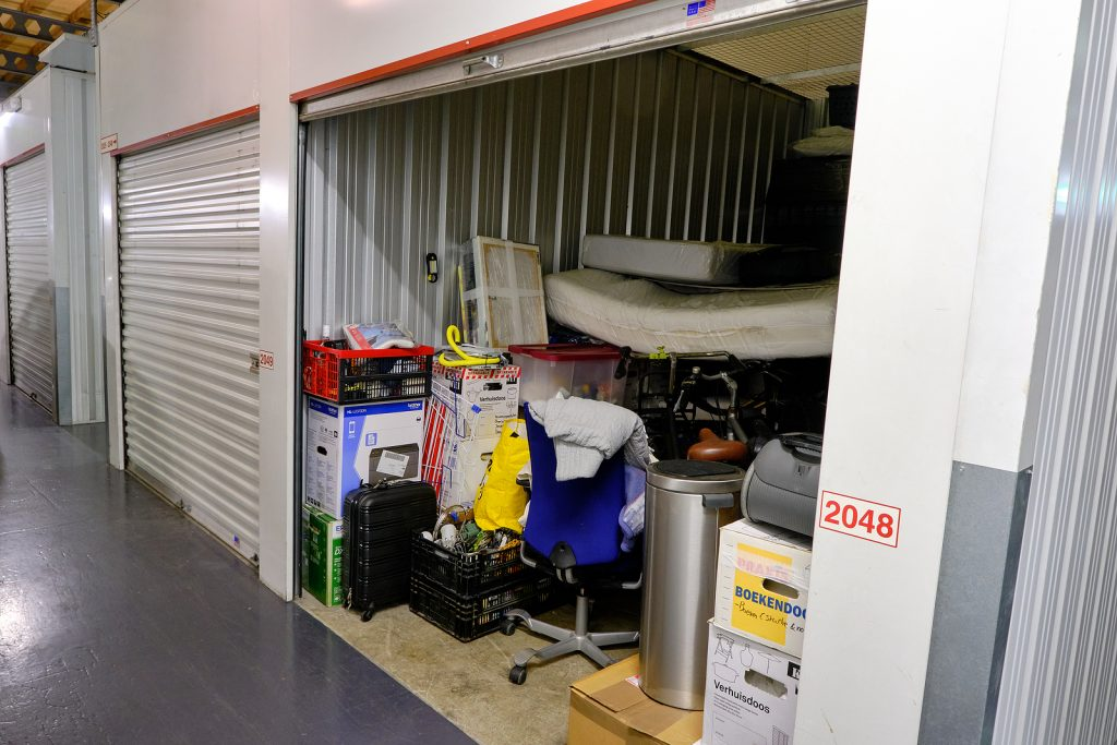 Indoor self storage unit with open door and household goods